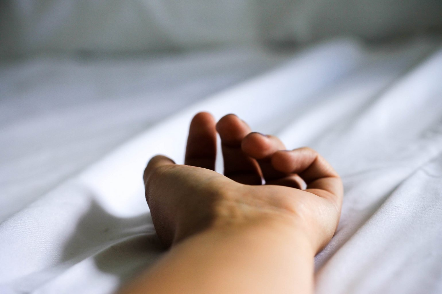 image of hand resting on a bed